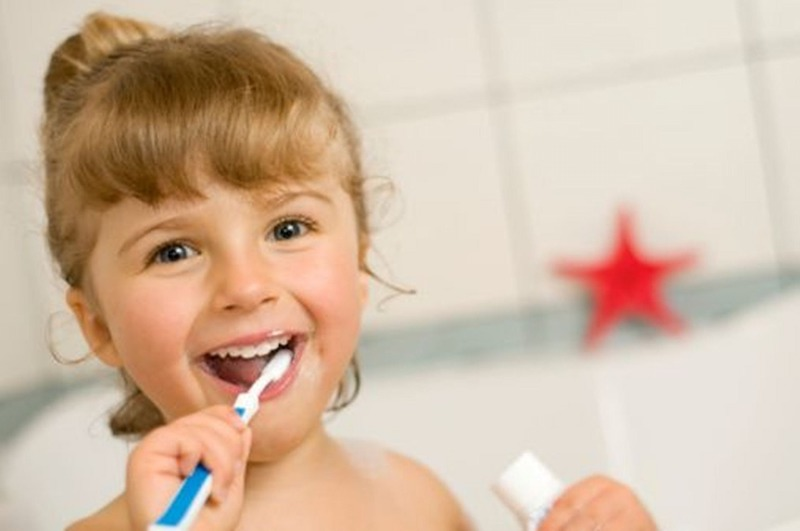 An adorable young girl brushes her teeth in the bathroom.